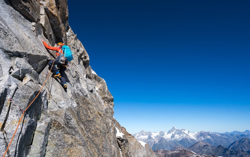 Alpine climber mountaineering on vertical rock face
